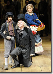 (Left to right) Paul Morland as A Beggar Child, Philip Pleasants as Ebenezer Scrooge and Christine Rowan as the Street Singer
