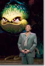Photo of Michael James Leslie (Voice of Audrey II). Audrey II puppeteered by Anthony Asbury, Michael Latini and Marc Petrosino